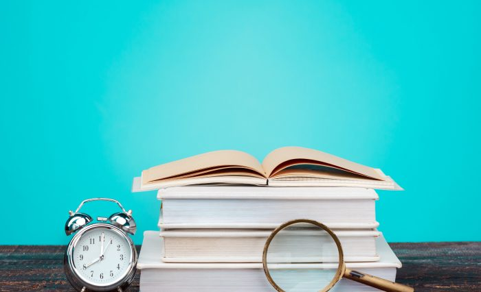 Back to School concept. School Books, colored pencils and clock on blue background